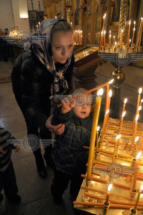 A mother helps her child light a candle at a Christmas service at an Orthodox church in Moscow.