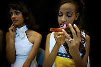 A contender for the crown works on her make up while a fellow participant speaks on her cell phone during the 2009 Miss Ethiopia beauty pageant held at the Intercontinental Hotel in Ethiopia's Capital Addis Ababa on Sunday January 18 2009.
