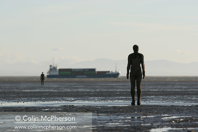 A container ship in the distance passes Antony Gormley's installation on Crosby beach near Liverpool on Merseyside entitled Another Place which consists of 100 six-foot bronze figures which are enveloped by the tide and revealed at low-tide on the sands. Gormley's figures were due to remain at Crosby until November 2006 after which they were to be moved to another location in another country. However a public campaign to keep the figures in Crosby permanently was successful in 2008..