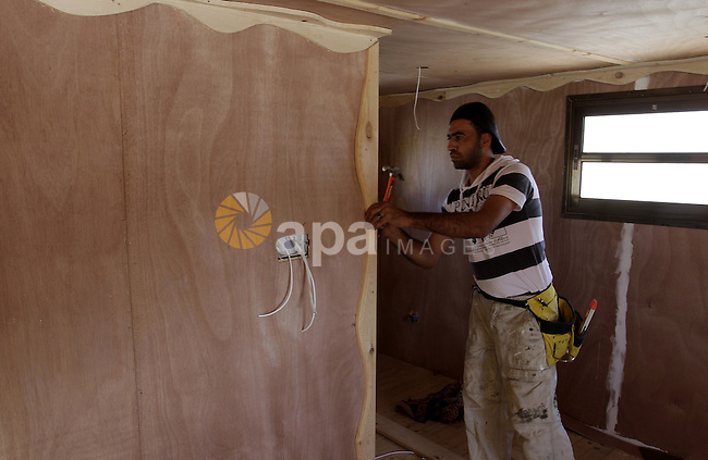 Palestinian carpenter Ibrahim Dokhan, 36, works using wood to rebuild a house, which was damaged during the recent Israeli offensive on Gaza Strip, in Rafah in the southern Gaza Strip, December 31, 2014. Because of the slow reconstruction process after three successive Israeli wars in the last six years have devastated the Gaza Strip, most recently the war in July that destroyed or damaged more than 84,000 houses, the pressing needs of Gazans has inspired innovators to develop solutions through available tools. Photo by Abed Rahim Khatib