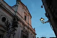 """taly. Apulia Region. Ceglie Messapica. Old town center. A Roman Catholic church at sunset. Street lamp post. Ceglie Messapica is a town and comune located in Apulia (Puglia), a region in Southern Italy. 6.12.18  © 2018 Didier Ruef<br /> <br /> <br /> <br /> <br /> <br /> <br /> Italy. Apulia Region. Locorotondo. The altar in Chiesa Rettoria Madonna della Greca (Church of Greca) is a  Roman Catholic church. A giant painting of the legend of Saint George and the Dragon which describes the saint taming and slaying a dragon that demanded human sacrifices; the saint thereby rescues the princess chosen as the next offering. Saint George was a Roman soldier of Greek origin and a member of the Praetorian Guard for Roman emperor Diocletian, who was sentenced to death for refusing to recant his Christian faith. He became one of the most venerated saints and martyrs in Christianity, and was especially venerated by the Crusaders. He is considered in catholic hagiography, as one of the Fourteen Holy Helpers and one of the most prominent military saints.  A catholic priest puts away at end of mass tall candlesticks. Locorotondo is a town and comune with a population of about 14,000. The city is known for its circular structure which is now a historical center, from which derives its name, which means """"Round place"""". Apulia (Puglia) is a region in Southern Italy. 5.12.18  © 2018 Didier Ruef"""