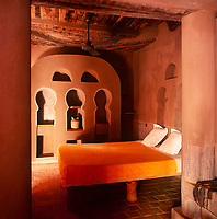 The interior of La Maison Rouge hotel with its distinctive red adobe contruction and Moroccan influence. A guest bedroom with a simple bed with a yellow cover.
