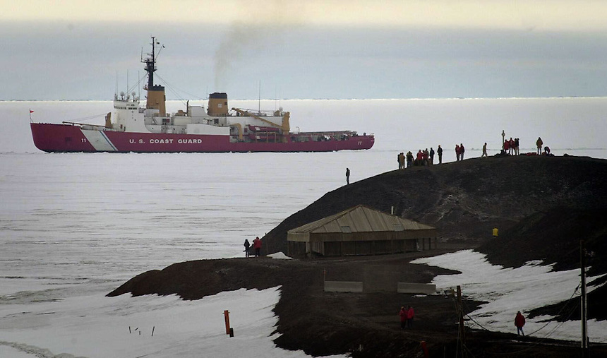 Residents of McMurdo Station, Antarctica stand on a hill near Scott's Hut as the US Coast Guard icebreaker Polar Sea breaks its way into port. It was New Year's Eve in broad daylight.