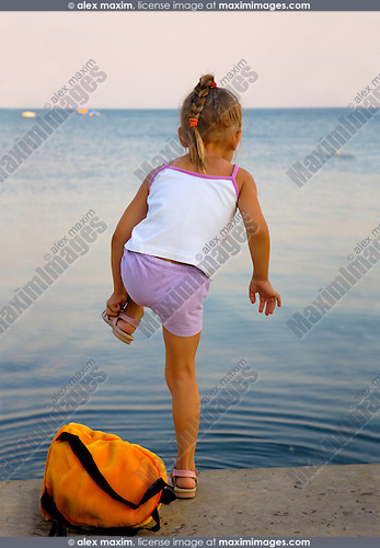 Little girl on a sea shore undressing going to swim in the sea Summer vacation and active lifestyle concept