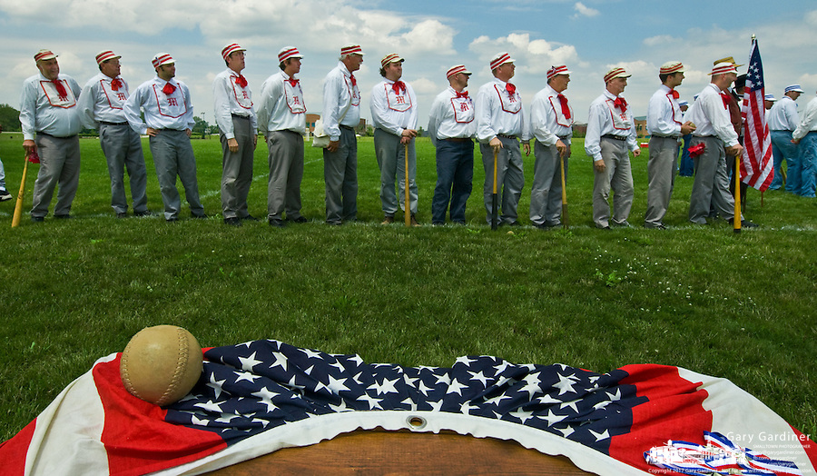 An antique baseball sits on red, white and blue bunting before a game with the Ohio Village Muffins who stand on the third base line for introductions.