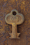 Small stubby old rusty key lying on metal sheet covered in identically coloured rust