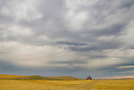 Abandoned red one room school house in harvested grain field, foreboding summer storm in rural Montana.