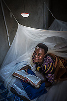 Uganda, Kakoula West. Jolly Bitature uses a Biolite stove as well solar lights in her home. She runs a business selling bananas. Here she's reading her bible at night using the solar light.