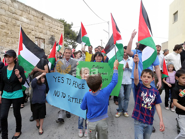 Demonstrators wave Palestinian flag during protest against the expropriation of Palestinian land to expand the Jewish settlement of Halmish on April 29, 2011 in the West Bank village of Nabi Saleh.. Photo by Issam Rimawi