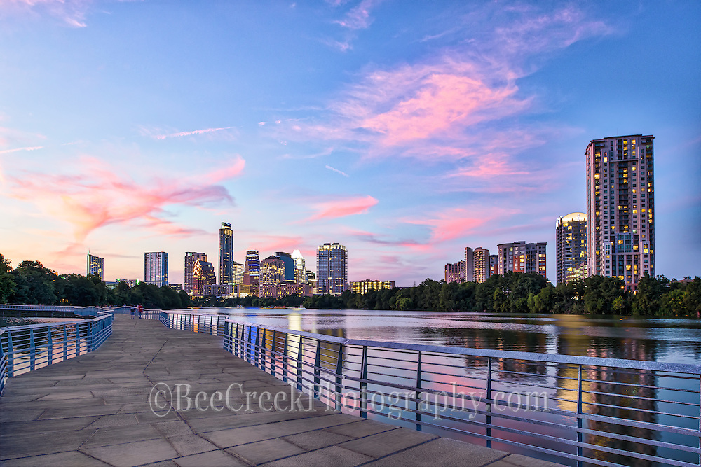 Austin skyline view from the boardwalk at sunset.  Another great sunset over the city of Austin from the new boardwalk.  I wanted to capture the boardwalk in my shot so it kind of leads the eye down the boardwalk to the Austin skyline with the pink clouds over the city.  Also the water picked up the pink colors of the sunset in the clouds and downtown buildings and left a pleasing reflection on the lake. The area along Ladybird lake or town lake as some call it is getting even more crowed with high rise buildings and is constantly evolving as we speak with new skycrapers.