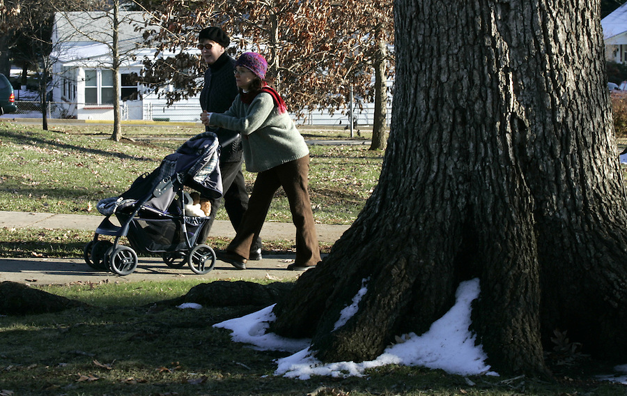 parent walking baby in stroller in park