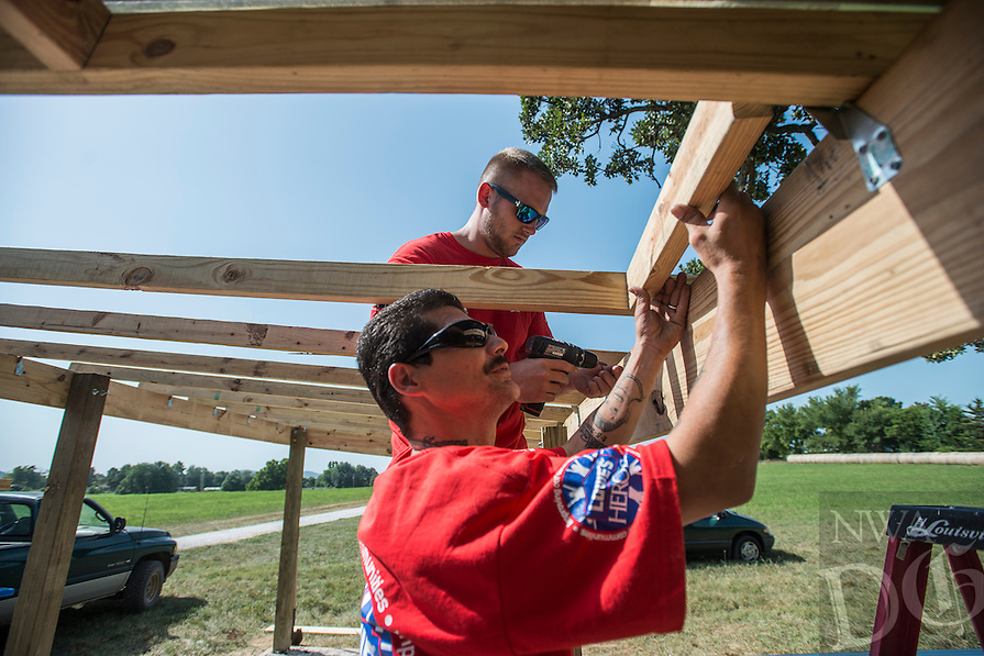 STAFF PHOTO ANTHONY REYES &bull; @NWATONYR<br /> Keith Myers, bottom, and Jordan Wallace, both with Lowes store 0432 in north Fayetteville, work on the rafters and roof Wednesday, Aug. 20, 2014 for a farm stand at Cobblestone Farms in Fayetteville. The pair are with the Lowes Heroes Project and join a crew in building the stand. Each store picks a community group to do a project for every year.