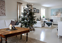 The spacious Swedish living room at Christmas is lit with subtle candlelight
