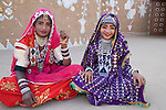 Rajasthani dancers wearing colorful, traditional costumes and jewelry, sitting in front of mud huts in desert camp, Thar Desert, Rajasthan, India --- Model Released
