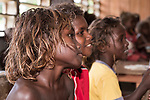 Peava Village, Gatokae Island, Solomon Islands; children sitting in their school classroom singing songs for the visiting tourists