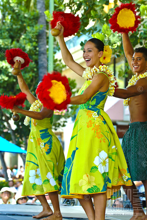 Kamehameha Schools hula dancers with red and yellow uli uli ( feathered gourd rattles ), plumeria lei and hibiscus flowers (the Hawaii state flower) in their hair at a performance in Waikiki