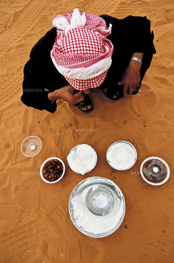 Saudi Arabia_Om Rogheiba_2002/12/15: 150km south of Hafar al Batin, about 400 km north of Riyadh near the border with Iraq. Hossein Alkhory, the organiser and communicating PR for all Bedouin's activities, drinking camel milk and eating dates which believes to be a staple food of desert nomad tribes..<br /> Arabie Saoudite. Om Rogheiba. 15/12/2002. A 150 km de Hafar al Batin, et a environ 400 km au nord de Ryad, pres de la frontiere iraquienne. Hossein Alkhory, organisateur et responsable de la communication pour toutes les manifestations des bedouins, buvant du lait de chamelle et mangeant des dattes, qui sont la nourriture de base des tribus nomades du desert.