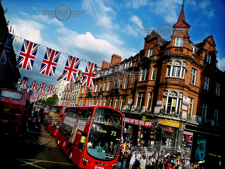 Buses drive down a street lined with Union Jack flags on the Diamond Jubilee of Queen Elizabeth II..