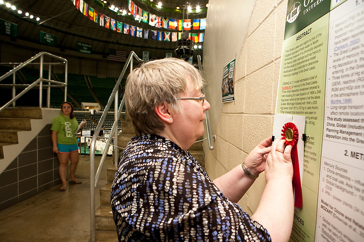 Pam Benoit affixes a prize to a Student Expo display.