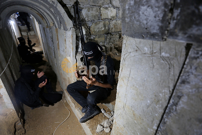 Palestinian militants guard the tunnel in the east of Gaza city on the Muslim holy fasting month of Ramadan on May 24, 2018. Ramadan is sacred to Muslims because it is during that month that tradition says the Koran was revealed to the Prophet Mohammed. The fast is one of the five main religious obligations under Islam. More than 1.5 billion Muslims around the world will mark the month, during which believers abstain from eating, drinking, smoking and having sex from dawn until sunset. Photo by Ashraf Amra
