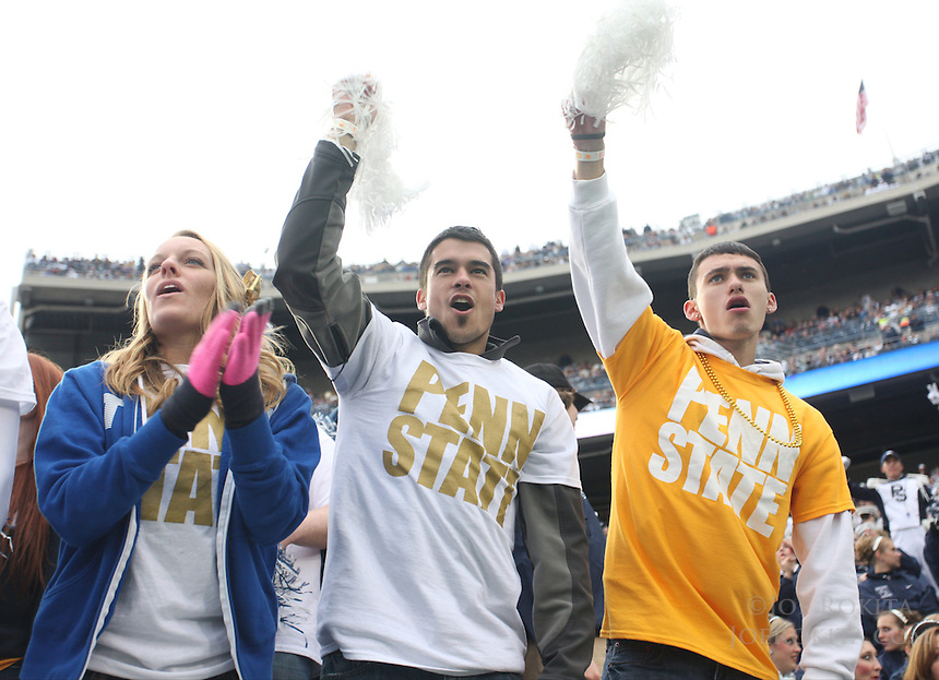 State College, PA - 11/02/2013:  PSU students Megan Raynor (left), Tyler Quinn (middle), and Michael Buchanan (right), cheer for their team.  They are wearing gold shirts to raise awareness for THON during the game.  Quinn is a Senior Mechanical Engineering student from Hanover, PA.  Penn State defeated Illinois by a score of 24-17 in overtime on Saturday, November 2, 2013, at Beaver Stadium.<br /> <br /> Photos by Joe Rokita / JoeRokita.com