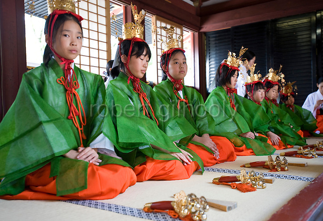 "Young ""yaotome"" female performers kneel in an antechamber during a ritual in the main hall of Tsurugaoka Hachimangu shrine during the second day of the 3-day Reitaisai grand festival in Kamakura, Japan on  15 Sept. 2012.  Photographer: Robert Gilhooly"