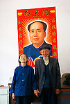 elderly Chinese couple at home below wall portrait of Chairman Mao Tse-tung in rural Three Gorges area of China, Asia