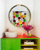 A brightly patterned wall is reflected in a round mirror in the small bathroom