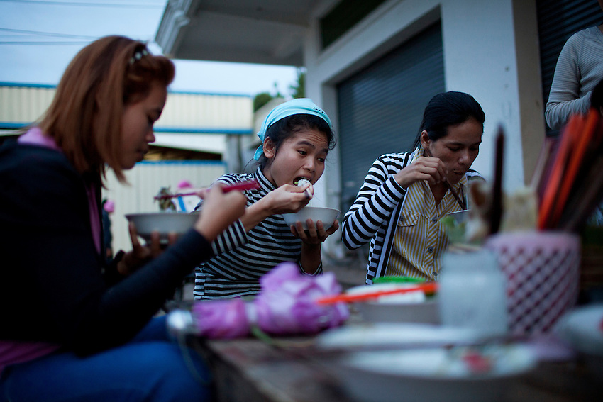 Workers eat noodles outside the Shen Zhou garment factory at 6 p.m. following the overtime shift, in Phnom Penh, Cambodia, Sept 12, 2011. A bowl of noodles at this particular shop costs about 25 cents (US). Standard hours at the factory are 7 a.m. to 4 p.m., with a 1-hour lunch break. Workers receive time and a half for the 2-hour overtime shift, which ends at 6 p.m.