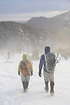 Couple of hikers (MR) dressed for the cold and wind, and prepared with mountaineering gear, in the krummholz near treeline, winter, Rocky Mountain National Park; blowing snow, February 2008, Colorado, USA, Rocky Mountains