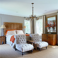 In the master bedroom a pair of Earl chairs stands at the foot of the bed with an antique door used as the headboard
