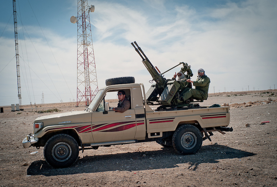 Rebel fighters man anti-aircraft gun during air raids by Gaddafi forces near Brega, Libya.