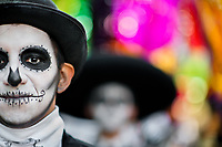 A young man, dressed as La Catrina, a Mexican pop culture icon representing the Death, walks through the town during the Day of the Dead parade in Mexico City, Mexico, 29 October 2016. Day of the Dead (Día de Muertos), a syncretic religious holiday combining the death veneration rituals of the ancient Aztec culture with the Catholic practice, is celebrated throughout all Mexico. Based on the belief that the souls of the departed may come back to this world on that day, people gather at the gravesites in cemeteries praying, drinking and playing music, to joyfully remember friends or family members who have died and to support their souls on the spiritual journey.