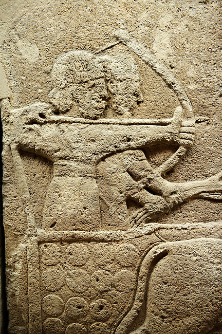 Picture & image of a Neo-Hittite orthostat with a chariot Releif sculpture from Karkamis,, Turkey. Museum of Anatolian Civilisations, Ankara. The Cahiot is pulled by horses with plumed headresses. One man os about to shoot an arrow from his bow, the other man is driving the cahriot. Below the horse is a animal cowering. 6