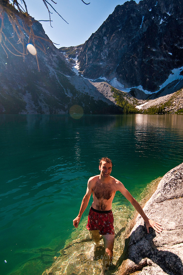 Smiling man getting out of alpine lake after swimming. Colchuck Lake, Alpine Lakes Wilderness, WA.