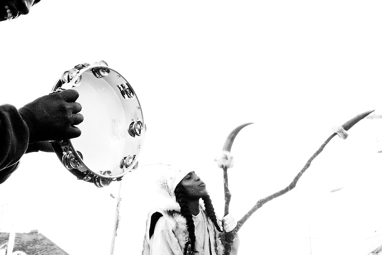 "A man bangs on a tambourine while Ruben Jones, ""flag boy"" of the Golden Comanches Mardi Gras Indians, sings along in New Orleans on February 28, 2006."