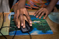Older girl helps a younger one during an IT literacy class organized by Phulki in a school in Mirpur, Dhaka. Schools are often the only places where children have access to computers and can learn computer skills.