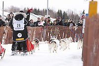 Saturday March 6 , 2010  A crowd of spectators along the trail during the ceremonial start of the 2010 Iditarod in Anchorage , Alaska cheer on Karen Ramstead and team .
