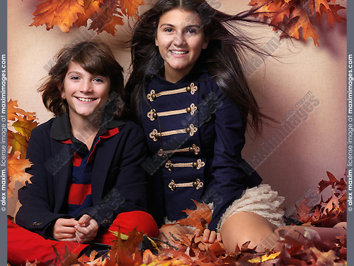 Smiling boy and a teenage girl in trendy clothes sitting together surrounded with red autumn leaves beautiful artistic fall fashion photo