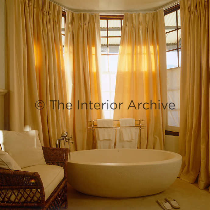 The full length curtains infuse this bathroom with golden light creating a relaxing atmosphere