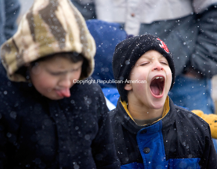 TORRINGTON, CT - 07 DECEMBER 2008 -120708JT14-<br /> Billy Baker, 6, right, of Torrington, and Daniel Layton, 8, of Winsted, try to catch snowflakes on their tongues during opening ceremonies outside the Christmas Village in Torrington on Sunday. The two were first in line, having had a relative hold their spot since 8:30 a.m. The Christmas Village is a 61-year tradition, featuring Santa Claus, Mrs. Claus, an elves' workshop, Christmas carols, a nativity scene, and animals. The village is free, but long lines are common. <br /> Josalee Thrift / Republican-American