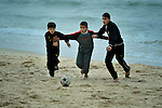Children play football along the beach in Gaza. Although the Palestinian territory fronts the sea, Gazans are not allowed to venture more than two kilometers from shore without coming under fire from Israeli gunboats..