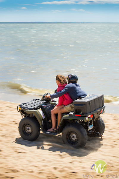 Hammonasset Beach State Park, New Haven County, Madison, Connecticut. Couple riding ATV on beach