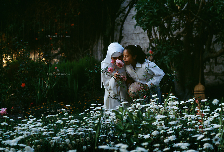 Novices stop and smell flowers in a garden during a break from their prayers and work at Santa Catalina Convent in Peru. Built in 1580 and enlarged in the 17th century, now 30 cloistered nuns live in privacy in the convent.  Five are novicias who study for five years to become a nun. The youngest nun is 15 and the oldest is 98. <br /> <br /> Novicias play with a soccer ball and sing together in the courtyard and the garden. Activities help the young girls adjust to the cloistered life.
