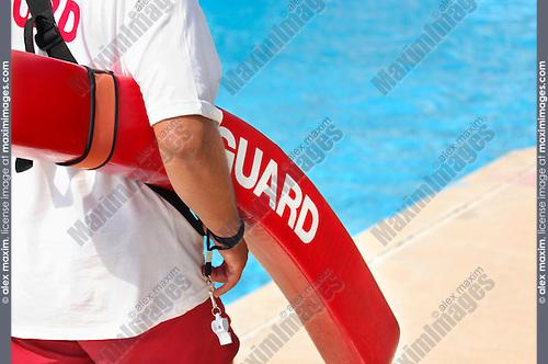 Life guard walking along a pool with a life saving buoy