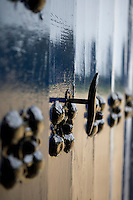 A close up of an iron key in a wooden door studded with a flower motif