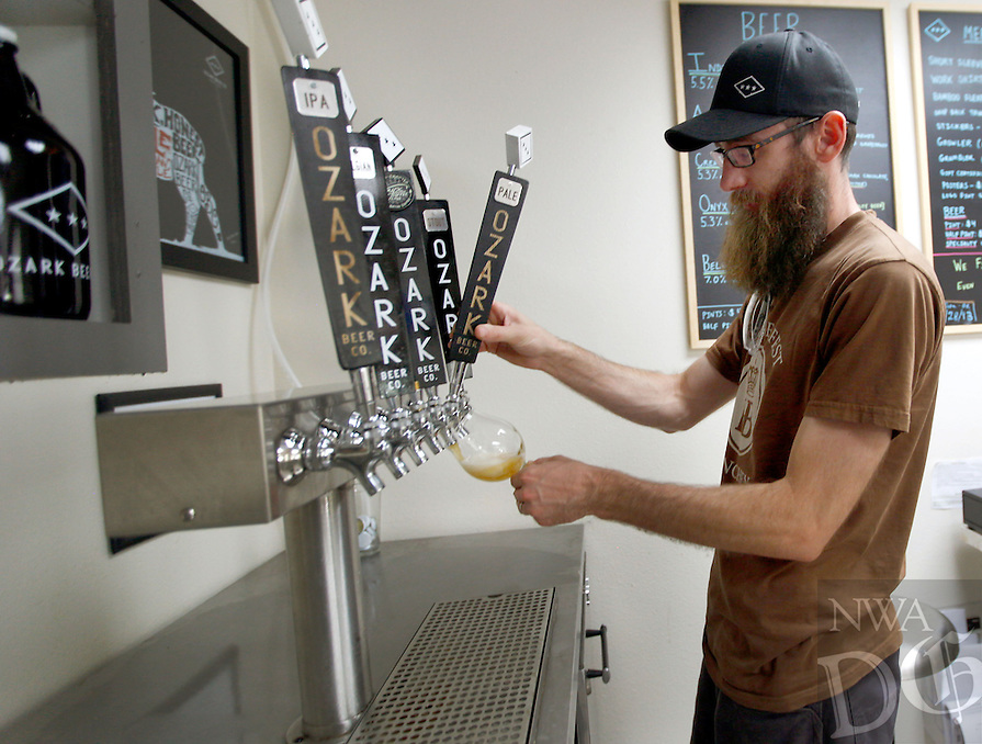 STAFF PHOTO JASON IVESTER --07/09/2014--<br />Andy Coates, one of three owners, pours a glass of their American pale ale in the tasting room on Wednesday, July 9, 2014, at Ozark Beer Company in Rogers. The brewery, which opened in November, has four brews -- India pale ale, APA, cream stout and Belgian style golden strong.