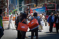 Joe Fresh shoppers seen in Times Square in New York on Thursday, June 20, 2013.  The Canadian retailer, founded by Joseph Mimran, (founder of Club Monaco), sells moderately and inexpensively priced apparel and was originally an exclusive product in the Canadian grocery chain, Loblaw's. (© Frances M. Roberts)