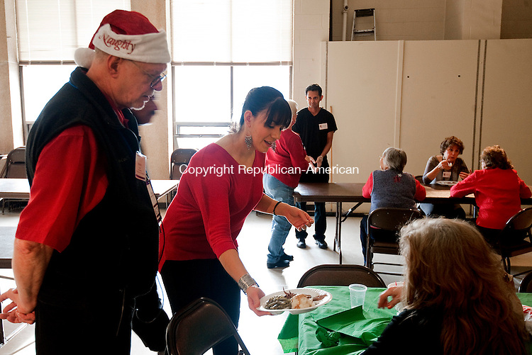 WATERBURY, CT--- -122515JS05--Kenneth Frazier, Jr., Senior Minister at the First Congregational Church in Waterbury, left, and volunteer Stacie Zindros, serve a dinner to a local resident during the annual Christmas Dinner Friday at the First Congregational Church in Waterbury. <br /> Jim Shannon Republican-American