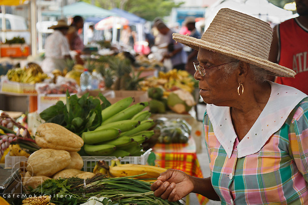 Elderly lady in a straw hat picks out her vegetables at the market in St Pierre, Martinique